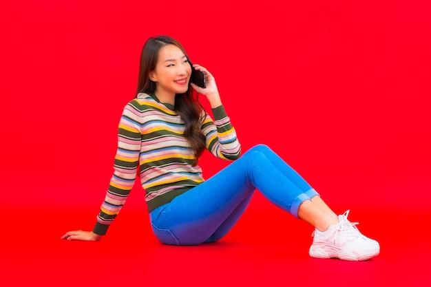 Portret piękna młoda azjatycka kobieta używa inteligentnego telefonu komórkowego na czerwonej ścianie na białym tle