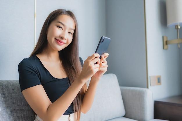Portret piękna młoda azjatycka kobieta używa inteligentnego telefonu komórkowego na kanapie w salonie