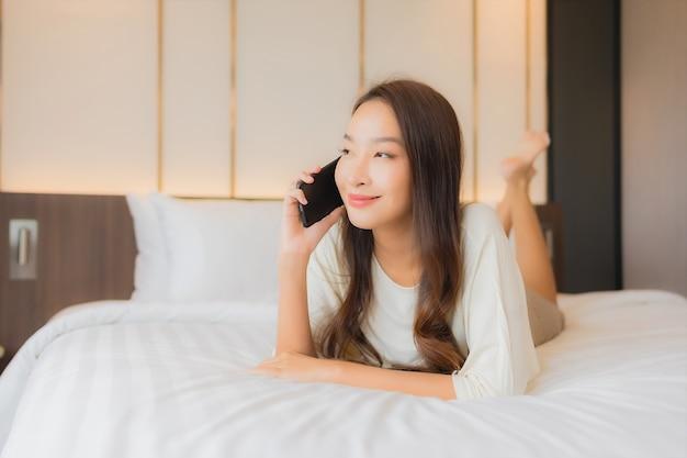 Portret piękna młoda azjatycka kobieta używa inteligentnego telefonu komórkowego na łóżku we wnętrzu sypialni