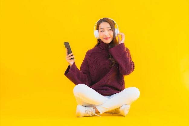 Portret piękna młoda azjatycka kobieta używa inteligentnego telefonu komórkowego słuchać muzyki