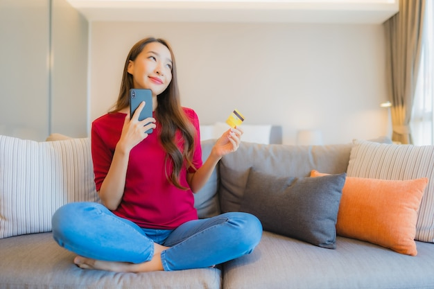 Portret piękna młoda azjatycka kobieta używa inteligentnego telefonu komórkowego z kartą kredytową