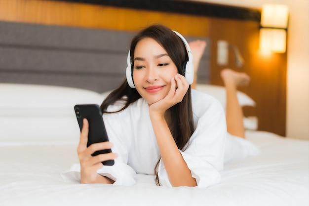 Portret piękna młoda azjatycka kobieta używa inteligentnego telefonu komórkowego ze słuchawkami do słuchania muzyki na łóżku we wnętrzu sypialni