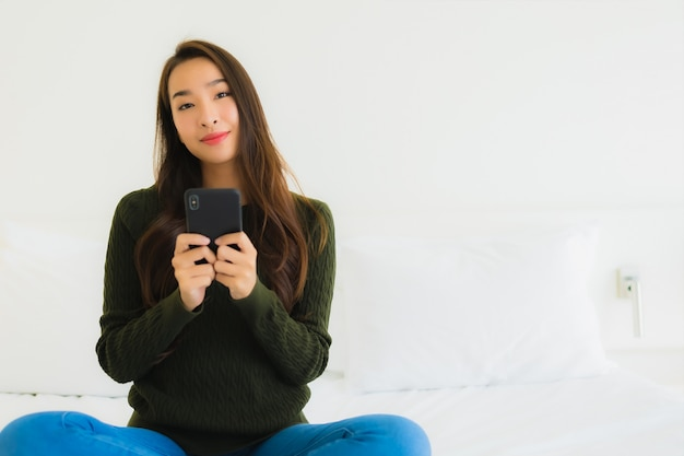 Portret piękna młoda azjatycka kobieta używa inteligentnego telefonu komórkowego