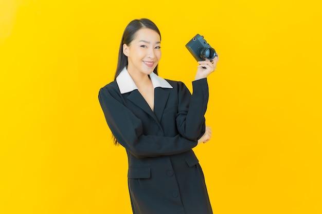 Portret piękna młoda azjatycka kobieta używa kamery na kolorowej ścianie