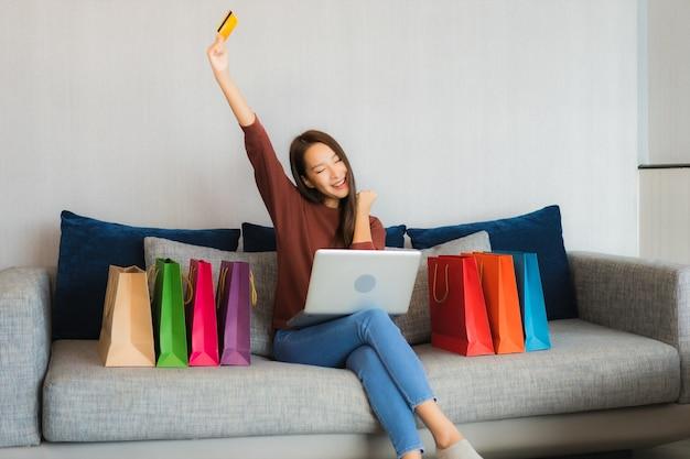 Portret piękna młoda azjatycka kobieta używa komputera laptop i karty kredytowej na zakupy online na kanapie w salonie