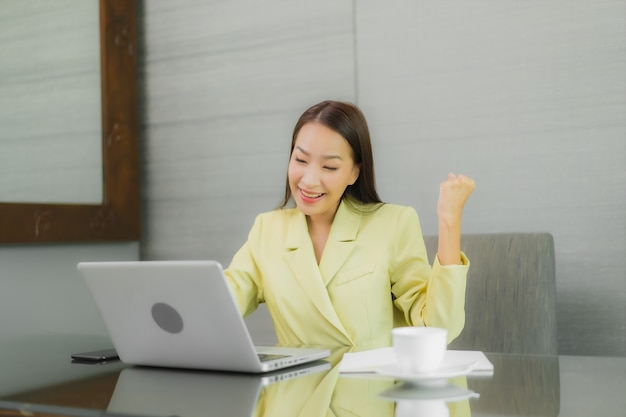 Portret piękna młoda azjatycka kobieta używa komputera laptop z inteligentny telefon komórkowy na stole roboczym w wnętrzu pokoju