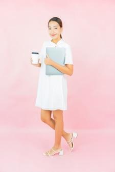 Portret piękna młoda azjatycka kobieta używa laptopa na różowej ścianie