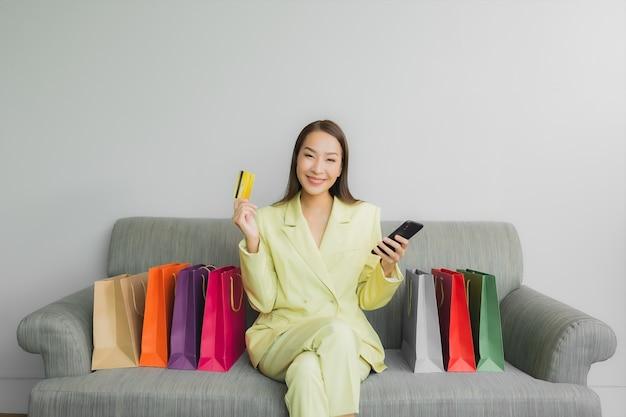 Portret piękna młoda azjatycka kobieta używa laptopa z kartą kredytową do zakupów online na kanapie we wnętrzu salonu
