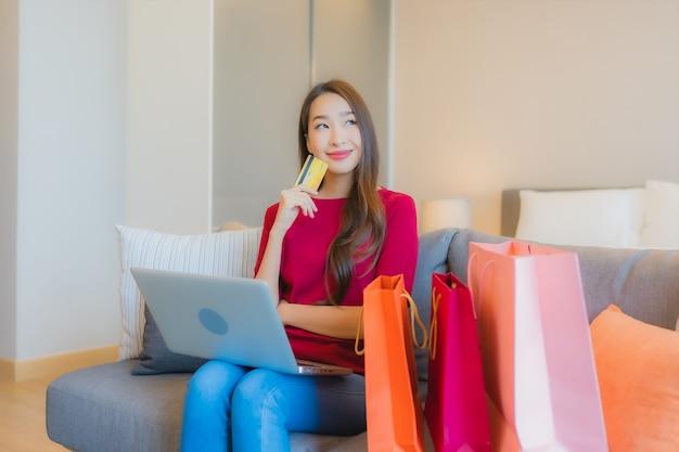 Portret piękna młoda azjatycka kobieta używa laptopa z kartą kredytową