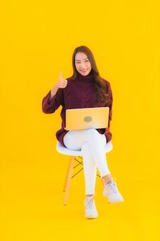 Portret piękna młoda azjatycka kobieta używa laptopa