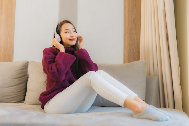 Portret piękna młoda azjatycka kobieta używa słuchawek do słuchania muzyki na kanapie we wnętrzu salonu