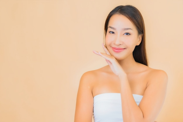 Portret piękna młoda azjatycka kobieta w spa z naturalnym makijażem na beżu