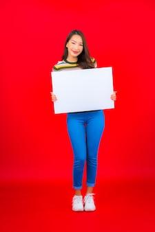 Portret piękna młoda azjatycka kobieta z białym pustym billboardem na czerwonej ścianie