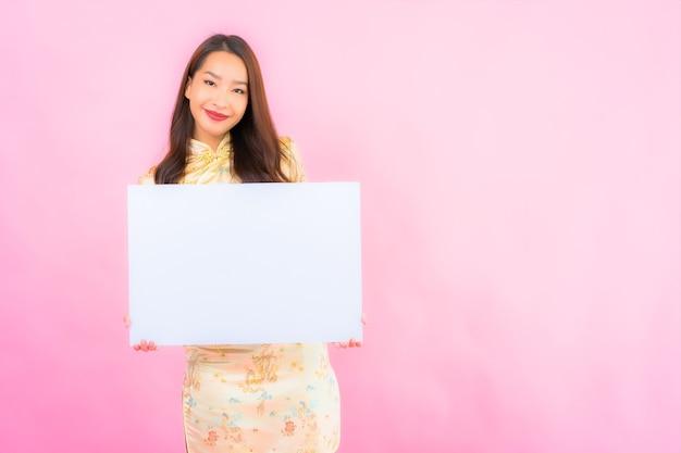 Portret piękna młoda azjatycka kobieta z białym pustym billboardem na różowej ścianie
