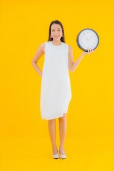 Portret piękna młoda azjatycka kobieta z budzikiem lub zegarem