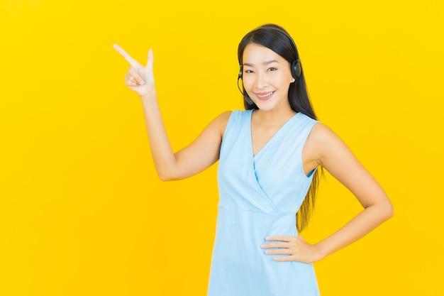 Portret piękna młoda azjatycka kobieta z centrum obsługi klienta call center na żółtej ścianie