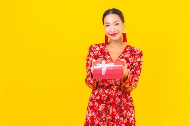 Portret piękna młoda azjatycka kobieta z czerwonym pudełkiem na ścianie koloru