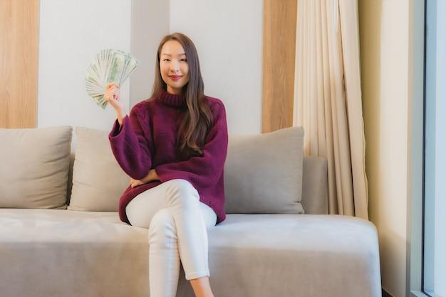Portret piękna młoda azjatycka kobieta z dużą ilością gotówki i pieniędzy na kanapie we wnętrzu salonu