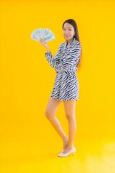Portret piękna młoda azjatycka kobieta z dużą ilością gotówki i pieniędzy na żółto