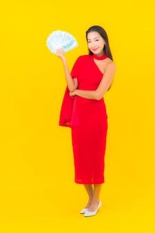Portret piękna młoda azjatycka kobieta z dużą ilością gotówki i pieniędzy