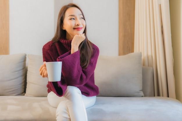 Portret piękna młoda azjatycka kobieta z filiżanką kawy na kanapie dekoracji wnętrza salonu