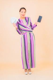 Portret piękna młoda azjatycka kobieta z gotówką lub pieniądze i inteligentny telefon komórkowy na kolor