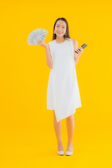 Portret piękna młoda azjatycka kobieta z gotówką