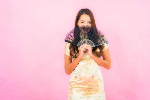 Portret piękna młoda azjatycka kobieta z koncepcją chińskiego nowego roku i wentylatorem na kolorowej ścianie