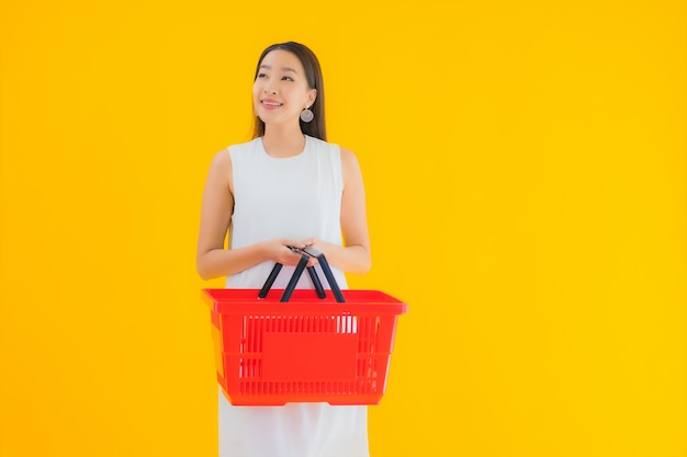 Portret piękna młoda azjatycka kobieta z koszykiem na zakupy w supermarkecie
