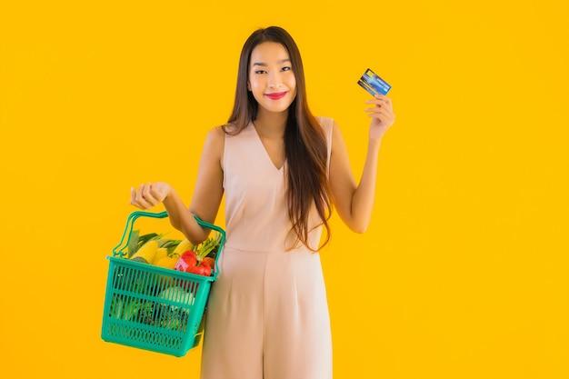 Portret piękna młoda azjatycka kobieta z koszykiem spożywczym