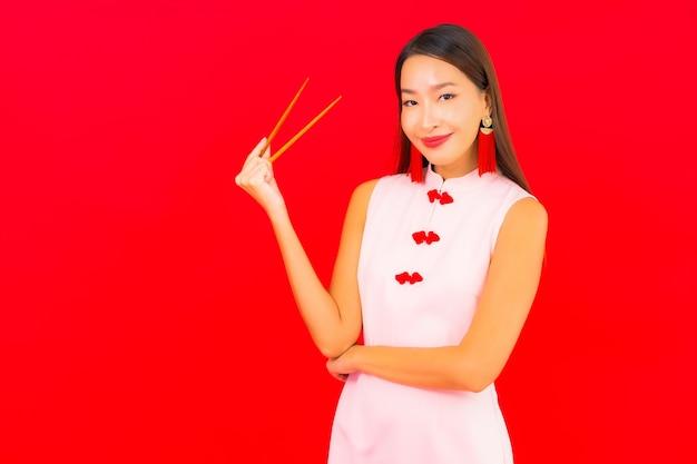 Portret piękna młoda azjatycka kobieta z pałeczkami na czerwonej izolowanej ścianie
