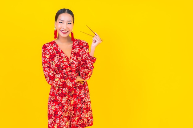Portret piękna młoda azjatycka kobieta z pałeczkami na kolor na białym tle ściany