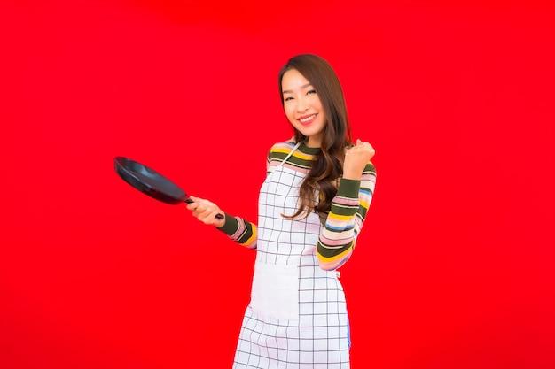 Portret piękna młoda azjatycka kobieta z patelni gotowy do gotowania na czerwonej ścianie