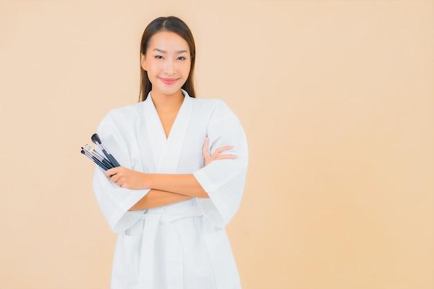 Portret piękna młoda azjatycka kobieta z pędzlem do makijażu na beżu