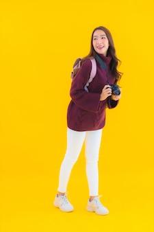 Portret piękna młoda azjatycka kobieta z plecakiem i aparatem do podróży na wakacje
