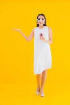 Portret piękna młoda azjatycka kobieta z popcornem i okularami 3d