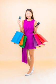 Portret piękna młoda azjatycka kobieta z torbą na zakupy na kolor na białym tle