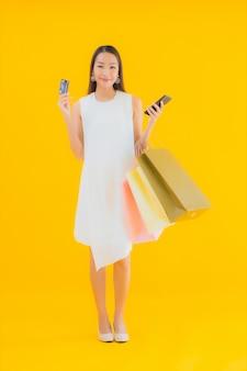 Portret piękna młoda azjatycka kobieta z torbą na zakupy z detalicznego domu towarowego
