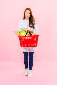 Portret piękna młoda azjatycka kobieta z warzywami owocowymi i sklepem spożywczym w koszu na różowej ścianie na białym tle