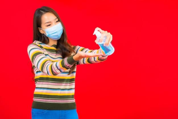 Portret piękna młoda azjatycka kobieta z żelem alkoholu na czerwonej ścianie na białym tle