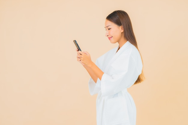 Portret piękna młoda azjatycka kobieta za pomocą inteligentnego telefonu komórkowego na beżu