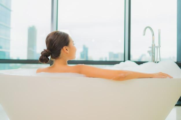 Portret piękna młoda azjatycka kobieta zrelaksować się uśmiech wypoczynek w wannie we wnętrzu łazienki