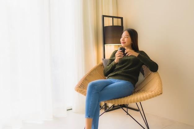 Portret piękna młoda azjatykcia kobieta chwyta filiżanka i obsiadanie na kanapy krześle