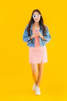 Portret piękna młoda azjatykcia kobieta cieszy się szczęśliwy z popkornem i ogląda film