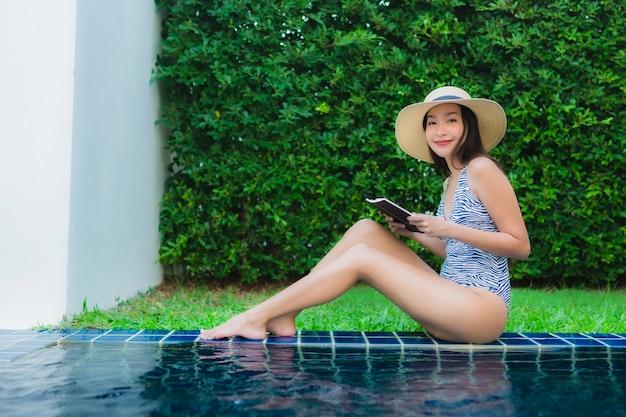 Portret piękna młoda azjatykcia kobieta czyta książkę wokoło pływackiego basenu