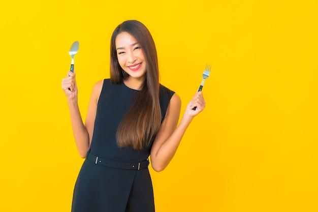 Portret piękna młoda azjatykcia kobieta gotowa do jedzenia z widelcem i łyżką na żółtym tle