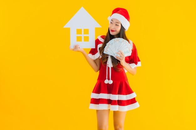 Portret piękna młoda azjatykcia kobieta jest ubranym boże narodzenie ubrania i kapeluszowy przedstawienie domu domu znak