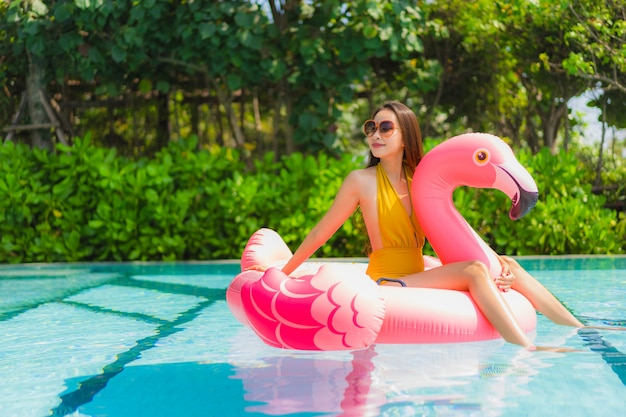 Portret piękna młoda azjatykcia kobieta na flaminga nadmuchiwanym pławiku w pływackim basenie przy hotelowym kurortem