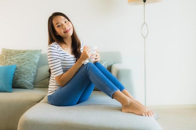 Portret piękna młoda azjatykcia kobieta na kanapie z filiżanką