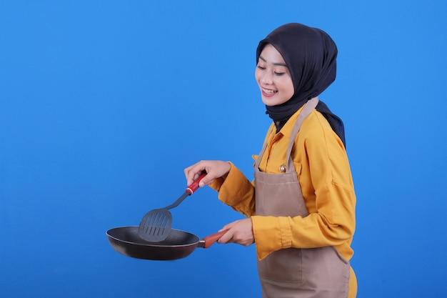 Portret piękna młoda azjatykcia kobieta nosi fartuch z czarną patelnią i łopatką